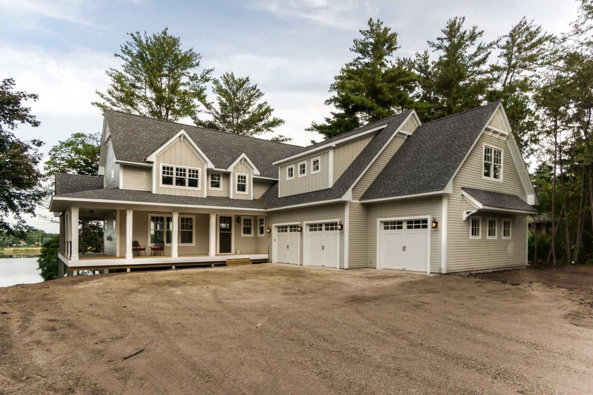 Front side view of Custom home with three stall garage and wrap around porch
