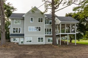 Rear view of custom home with wrap around porch and trees