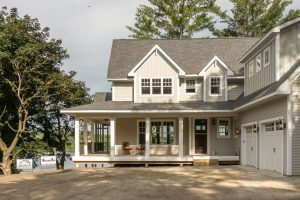 Front view of custom home with wrap around porch and trees, Xpand Inc.