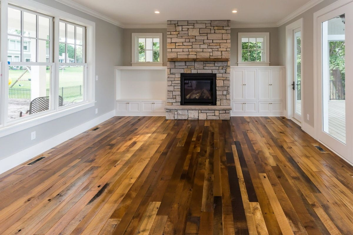 family room with fire place and hardwood floor and door leading to wrap around porch and windows all around the room