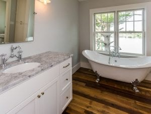 Master bath with hardwood floor and window overlooking lake
