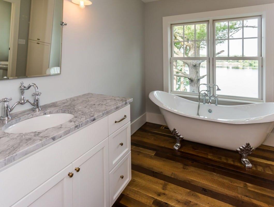 Master bath with hardwood floor and window overlooking lake