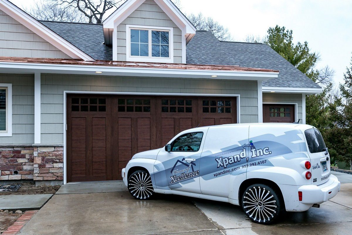 Xpand Inc and homes of xcellence car in front of house