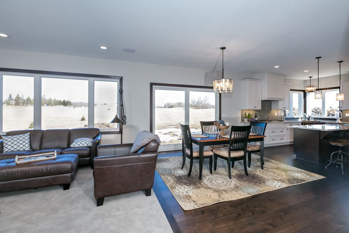 living room with carpet leading into dining room with hardwood floors