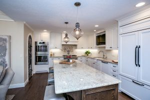Kitchen counter and stainless steel stove, an island and tile backdrop on the wall