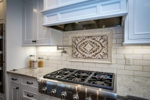 Kitchen counter and stainless steel stove with tile backdrop on the wall