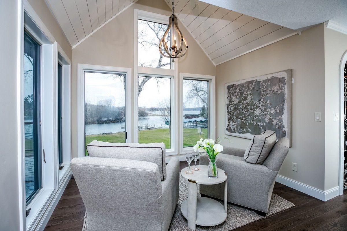 Sitting area overlooking backyard and lake with chandelier