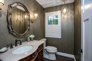 half bathroom with small window and chandelier