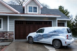 Xpand inc & Homes of Xcellence car in front of house