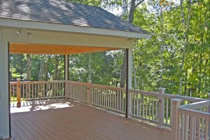 deck with white wood material in backyard with many trees.