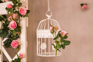 Shabby chic decorating with beautiful vintage birdcage and flowers.