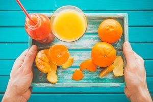 Man holds a vintage tray with mandarins and fresh juice in her hands. Top view