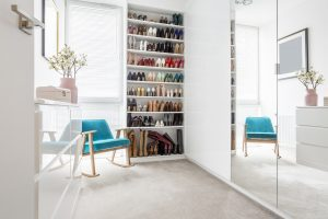 Large shoe wardrobe next to a blue, comfortable chic chair standing in a woman's white room