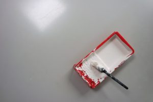 white paint in a red tray used for painting a gray wall