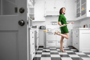 women dancing around joyfully with a broom in her kitchen
