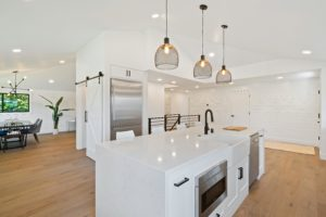 modern white kitchen with an island and overhanging lights