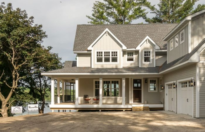 Front view of custom home with wrap around porch and trees