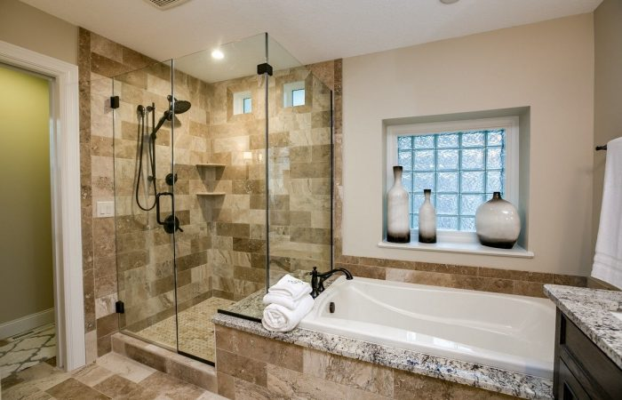 Master Bathroom with standing glass shower and a tub