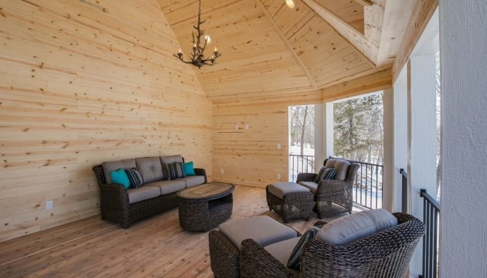 Covered deck view with outdoor furniture and wood finish with a chandelier made from antlers