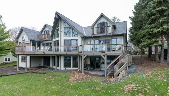 Back right view of custom home with large deck on main level and 2 small walkouts on the upper level
